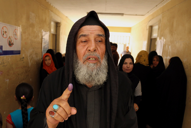 Description of . An Iraqi elderly man shows his ink-stained finger after casting his vote inside a polling station for parliamentary elections in Baghdad, Iraq, Wednesday, April 30, 2014. Iraq is holding its third parliamentary elections since the U.S.-led invasion that toppled dictator Saddam Hussein. More than 22 million voters are eligible to cast their ballots to choose 328 lawmakers out of more than 9,000 candidates. (AP Photo/Karim Kadim)
