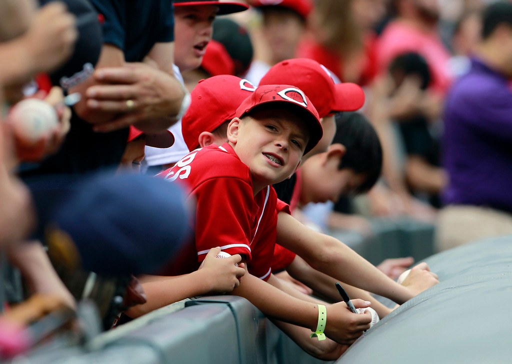 . Cincinnati Reds fans seek autographs from players before the Reds face the Colorado Rockies in a baseball game in Denver, Sunday, Sept. 1, 2013. (AP Photo/David Zalubowski)