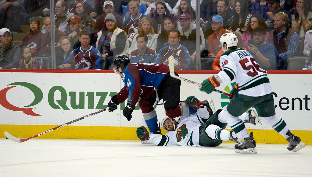 . DENVER, CO - APRIL 26: Minnesota Wild right wing Justin Fontaine (14) gets taken down by Colorado Avalanche left wing Gabriel Landeskog (92) during the third period of action. The Colorado Avalanche hosted the Minnesota Wild in the fifth round of the Stanley Cup Playoffs at the Pepsi Center in Denver, Colorado on Saturday, April 26, 2014. (Photo by John Leyba/The Denver Post)