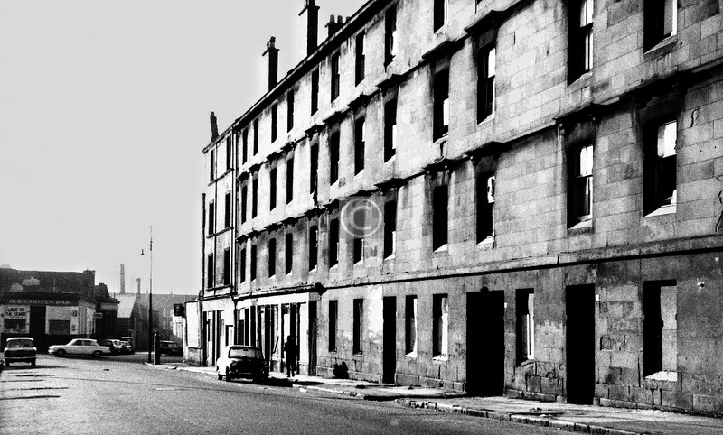 Sydney St, west side.  Looking down to the Gallowgate and on to Lambert St, with the Old Canteen Bar on the corner and , the dark building dimly seen beside the pub, the former Gallowgate Central Station, which had been closed since 1917.    January 1974