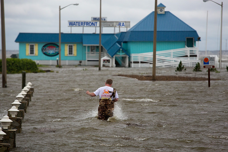 . Bryan Wilson, owner of Millerís Waterfront restaurant, braves floodwaters to check the damage to his property as wind from the Hurricane Arthur pushes water to his parking lot in Nags Head, N.C. Friday, July 4, 2014. Arthur struck North Carolina as a Category 2 storm with winds of 100 mph late Thursday, taking about five hours to move across the far eastern part of the state. (AP Photo/The Virginian-Pilot, Hyunsoo Leo Kim)