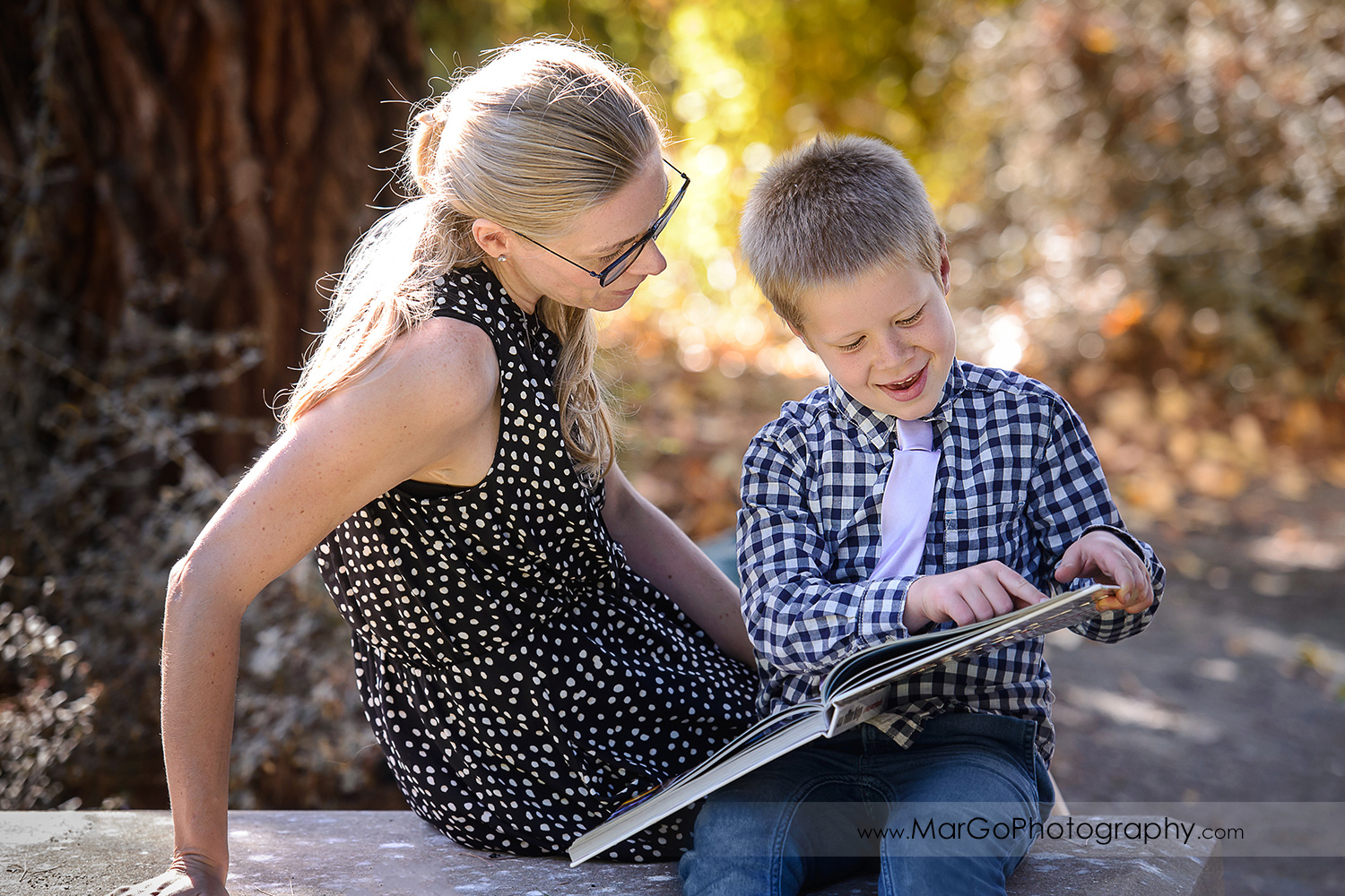 young boy showing mom something in the book at Mountain View Shoreline Lake Park