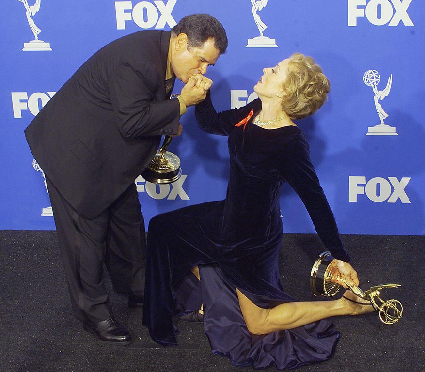 """. Actors Michael Badalucco (L) kisses the hand of co-star Holland Taylor (R) as they pose with their Emmy Award for Outstanding Supporting Actor and Actress for a Drama Series for their roles in \""""The Practice\"""" at the 51st Emmy Awards at the Shrine Auditorium in Los Angeles 12 September, 1999.  Scott Nelson/AFP/Getty Images"""
