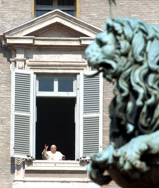 . Pope John Paul II is framed by a bronze lion as he blesses pilgrims and faithful during a surprise appearance at the open window of  his studio overlooking St. Peter\'s Square at the Vatican, Wednesday, March 16, 2005. This is the first time he has been seen since  his release from hospital Sunday March 13. (AP Photo / Massimo Sambucetti)