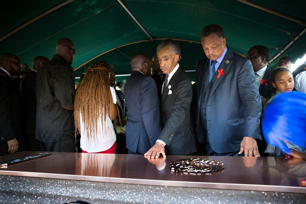 Description of . Rev. Al Sharpton and Jessie Jackson touch the casket during the funeral for Michael Brown at St. Peters Cemetery on August 25, 2014 in St. Louis Missouri. Michael Brown, an 18 year-old unarmed teenager, was shot and killed by  Ferguson Police Officer Darren Wilson in the nearby town of Ferguson, Missouri on August 9. His death caused several days of violent protests along with rioting and looting in Ferguson.  (Photo by Richard Perry-Pool/Getty Images)