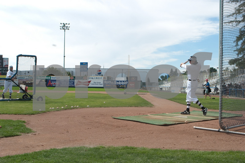 Batting practice uses a barrier to protect the pitcher and a carpet marked with a home plate and guidance stripes.