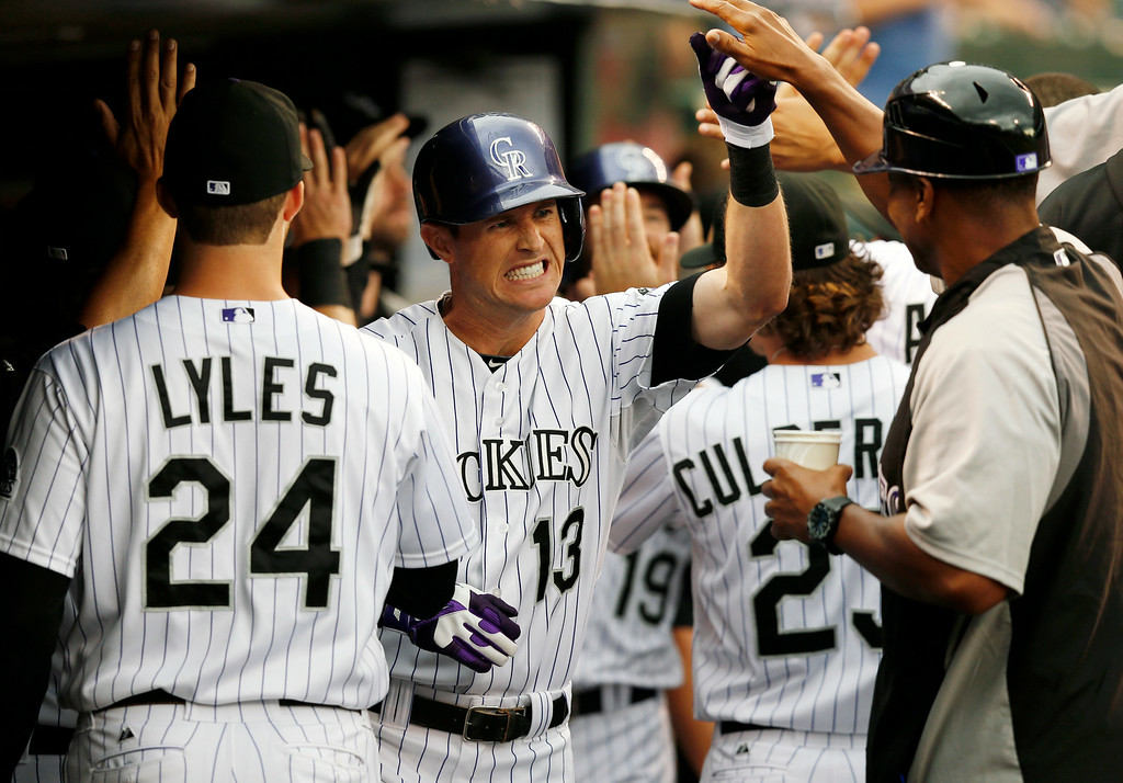 . Colorado Rockies\' Drew Stubbs (13) is congratulated by teammates in the dugout after hitting a two run home run off Minnesota Twins starting pitcher Kris Johnson during the first inning of a baseball game on Friday, July 11, 2014, in Denver. (AP Photo/Jack Dempsey)
