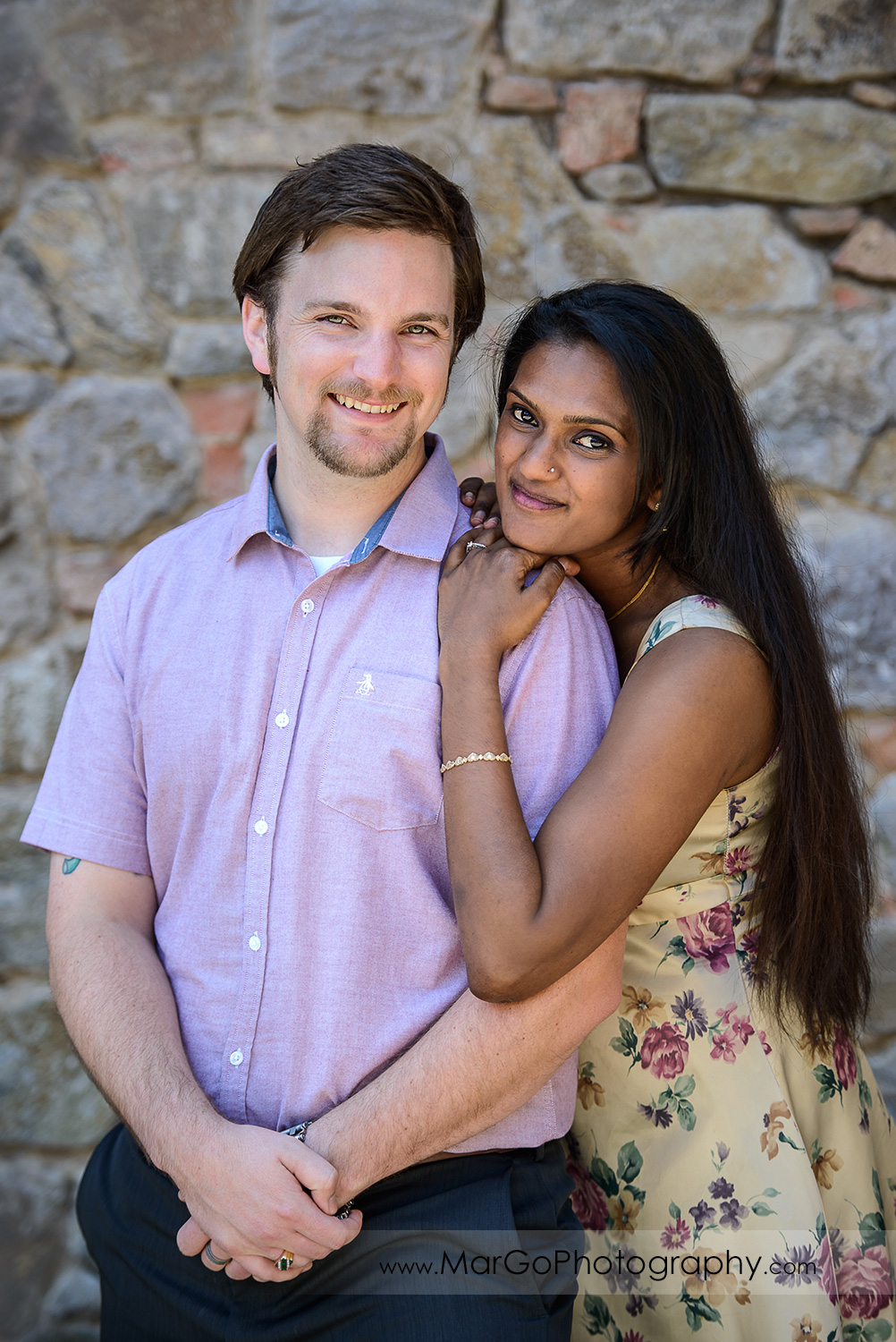 portrait of Indian woman in flower dress and man in pink shirt lokking into camera on brick background during engagement session at Castello di Amorosa in Calistoga