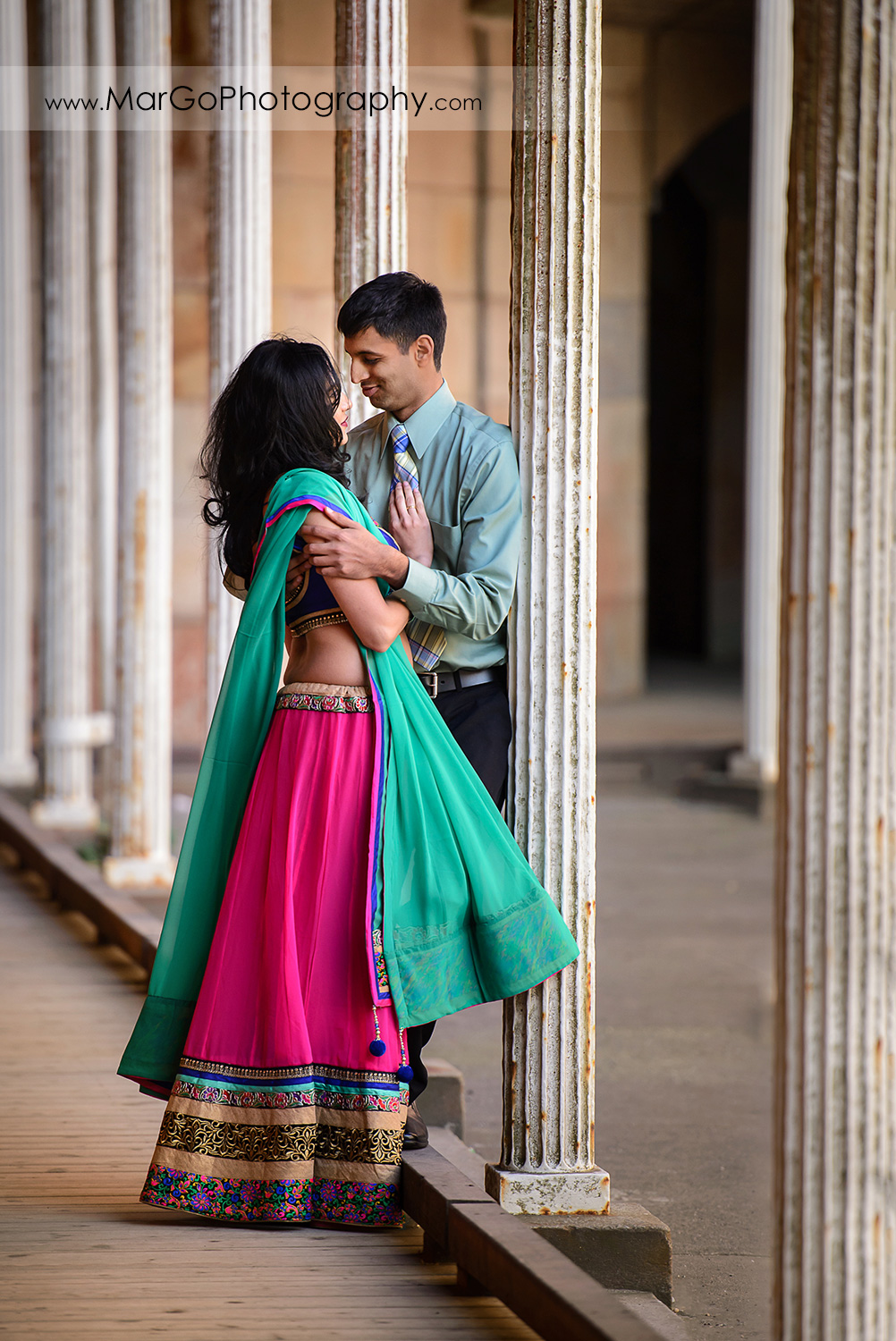 full body portrait of Indian couple in green clothes  on the white columns of San Francisco Fort Point during engagement session
