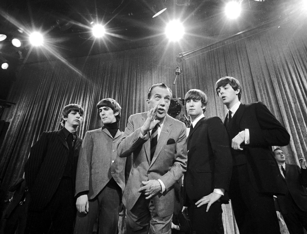 ". Ed Sullivan, center, stands with The Beatles during a rehearsal for the British group\'s first American appearance, on the ""Ed Sullivan Show,"" in New York on Feb. 8, 1964. From left:  Ringo Starr, George Harrison, Sullivan, John Lennon and Paul McCartney. The rock \'n\' roll band known as ""The Fab Four"" was seen by 70 million viewers. ""Beatlemania"" swept the charts with twenty No. 1 hits and more than 100 million records sold.  The Beatles broke up in 1970. (AP Photo)"