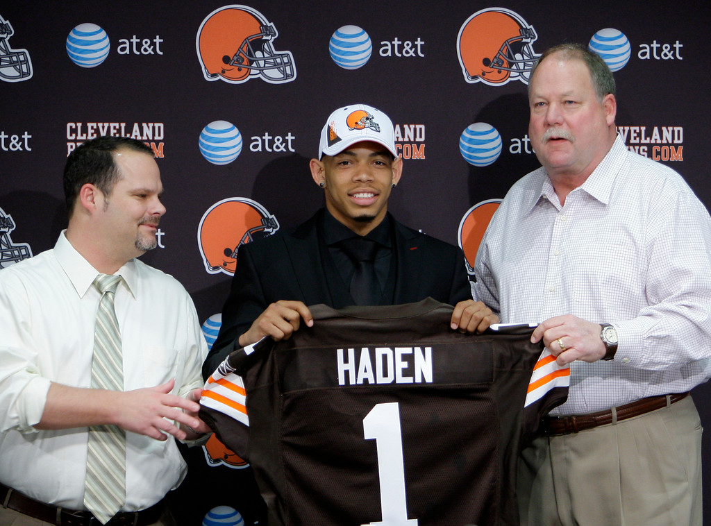 . Cleveland Browns general manager Tom Heckert, left, and president Mike Holmgren, right, present a jersey to first round draft pick Joe Haden at the NFL football team\'s headquarters in Berea, Ohio on Friday, April 23, 2010. The Browns took the Florida cornerback with the seventh overall pick in the 2010 draft. (AP Photo/Mark Duncan)