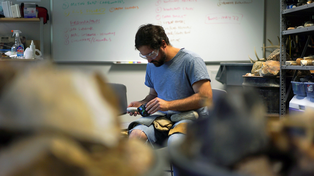 . In this June 1, 2017, photo, Metin Eren, an archaeologist at Kent State University, pauses while chipping obsidian in Kent, Ohio. Eren runs a newly-opened laboratory which makes replicas of ancient arrows, knives, and pottery to be shot, crushed, and smashed. It\'s allowing researchers to learn about engineering techniques of the first native Americans without destroying priceless genuine relics in the process. (AP Photo/Dake Kang)