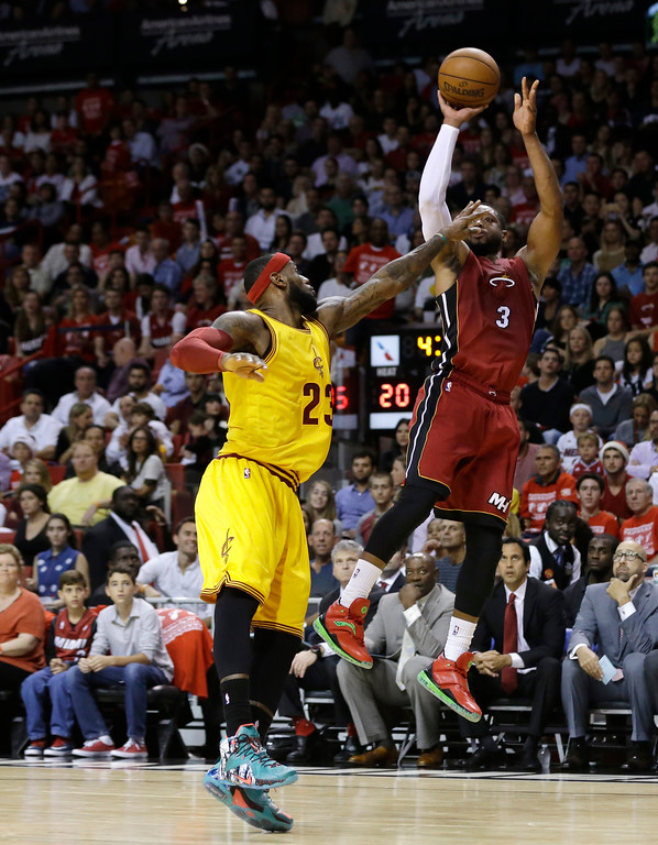 . Miami Heat guard Dwyane Wade (3) shoots over Cleveland Cavaliers forward LeBron James (23) during the first half of an NBA basketball game, Thursday, Dec. 25, 2014, in Miami. (AP Photo/Lynne Sladky)