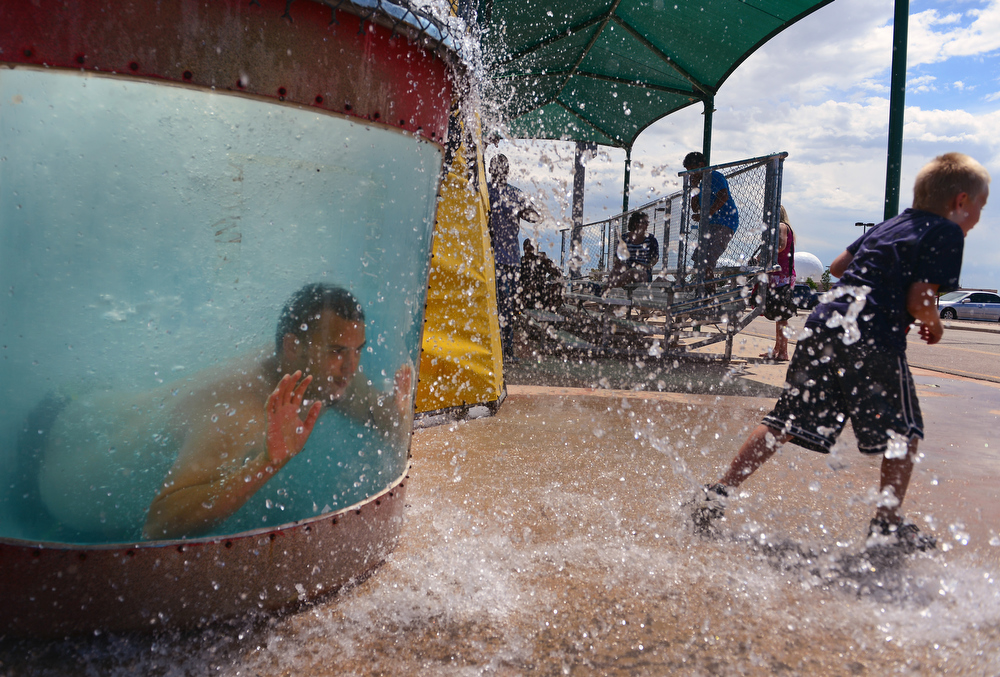 . Cody Morris, 6, right, tries to get away from the splashing water after watching A1C Andrew McCormick of the 140th Maintenance Wing get dunked in the dunking pool at Buckley Air Force base in Aurora, CO on August 4, 2013.  The event was part of the 140th Wing Family Day for members of the Colorado National Guard.  Much of the money raised during the day goes to the Colorado National Guard Family Support System that helps take care of families when their loved ones have been deployed.  The Salvation Army was on hand to show their continued support for the armed services.  Photo by Helen H. Richardson/The Denver Post)