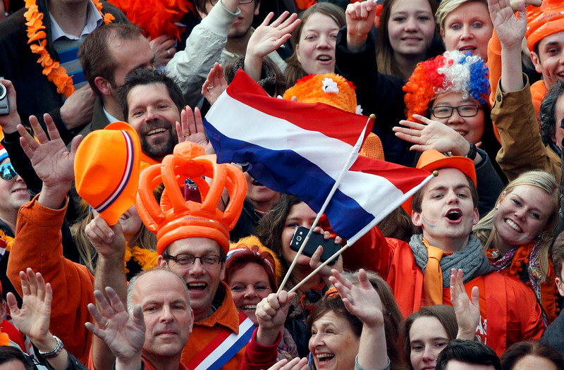 . People celebrate the new Dutch King Willem-Alexander who succeeds his mother Queen Beatrix, in Amsterdam\'s Dam Square April 30, 2013. Queen Beatrix of the Netherlands abdicated on Tuesday, handing over to her eldest son, Willem-Alexander, who became the first King of the Netherlands in over 120 years.  REUTERS/Kevin Coombs
