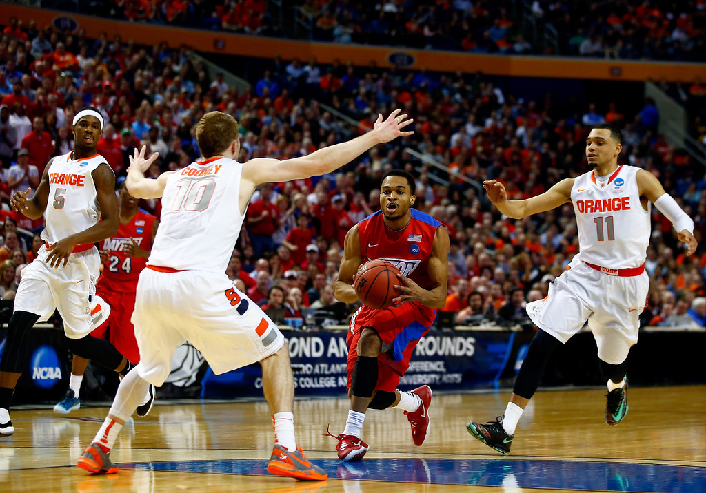 . BUFFALO, NY - MARCH 22: Vee Sanford #43 of the Dayton Flyers drives to the basket as Trevor Cooney #10 of the Syracuse Orange defends during the third round of the 2014 NCAA Men\'s Basketball Tournament at the First Niagara Center on March 22, 2014 in Buffalo, New York.  (Photo by Jared Wickerham/Getty Images)
