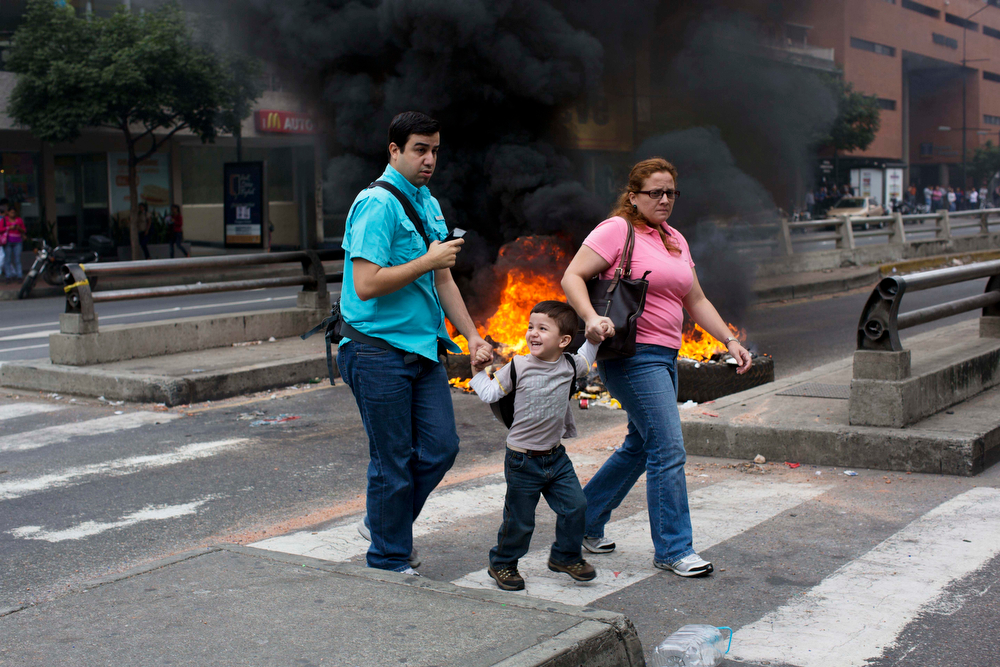 . People walk in front of a burning barricade blocking the highway in Chacao, Caracas, Venezuela, Monday, Feb. 24, 2014. Traffic has come to a halt in parts of the Venezuelan capital because of barricades set up by opposition protesters across major thoroughfares. The protests are part of a wave of anti-government demonstrations that have swept Venezuela since Feb. 12 and have resulted in at least 10 deaths. The protests in the capital Monday were peaceful. Police and National Guard troops stood by but did not act to remove the barricades despite the effect on the morning commute. (AP Photo/Rodrigo Abd)