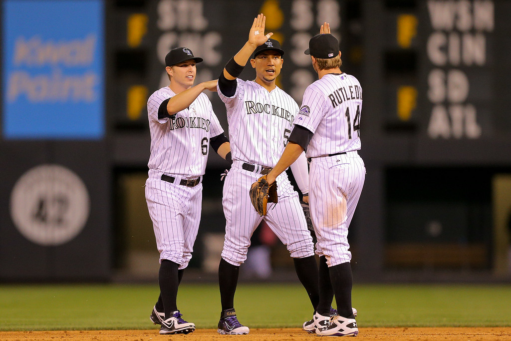 . Corey Dickerson #6, Carlos Gonzalez #5 and Josh Rutledge #14 of the Colorado Rockies celebrate their win against the Pittsburgh Pirates at Coors Field on July 25, 2014 in Denver, Colorado. The Rockies defeated the Pirates 8-1. (Photo by Justin Edmonds/Getty Images)