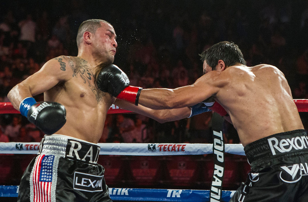 . Mike Alvarado, left, and Juan Manuel Márquez, of Mexico, exchange punches in the fourth round of a WBO welterweight title boxing match at the Forum in Inglewood, Calif., Saturday, May 17, 2014. Márquez won the title.  (AP Photo/Ringo H.W. Chiu)