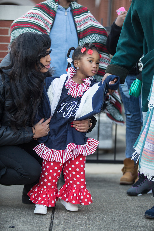 . Jaclyn Banks, 3, of Mobile, Ala., peeks across the street beside her mother Kiara on Saturday, March 7, 2015, while waiting in line to see President Barack Obama speak to commemorate the 50th anniversary of Bloody Sunday and the Selma-to-Montgomery voting rights march in Selma, Ala. (AP Photo/Casper Star-Tribune, Ryan Dorgan)
