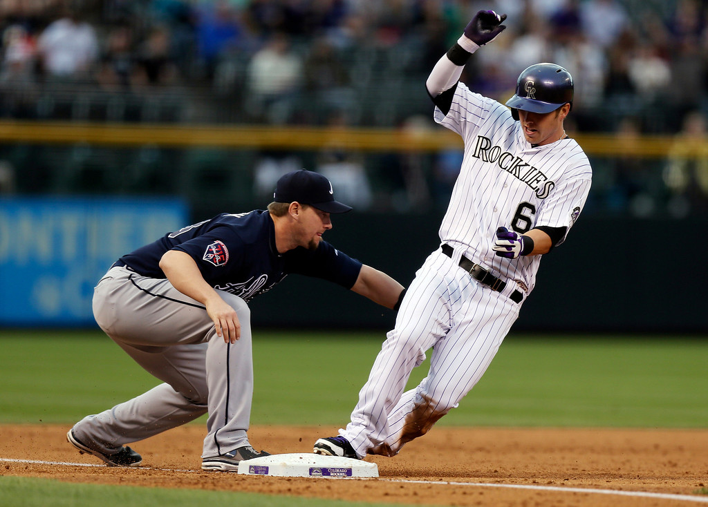 . Colorado Rockies\' Corey Dickerson, right, makes it safely to third base after hitting a triple to drive in two runs as Atlanta Braves third baseman Chris Johnson applies the tag in the first inning of a baseball game in Denver on Wednesday, June 11, 2014. (AP Photo/David Zalubowski)