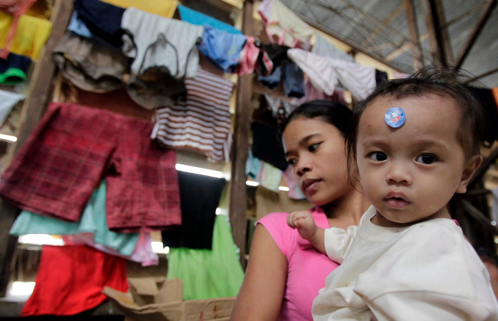 Description of . A mother holds her child at a gymnasium, turned into an evacuation centre for residents who were rendered homeless after their houses were swept by floodwaters at the height of Typhoon Bopha, in New Bataan town in Compostela Valley, southern Philippines December 8, 2012. Philippine President Benigno Aquino declared a state of national calamity on Saturday, four days after this year\'s strongest typhoon left nearly 1,000 people dead or missing mostly in the country\'s resource-rich south. REUTERS/Erik De Castro