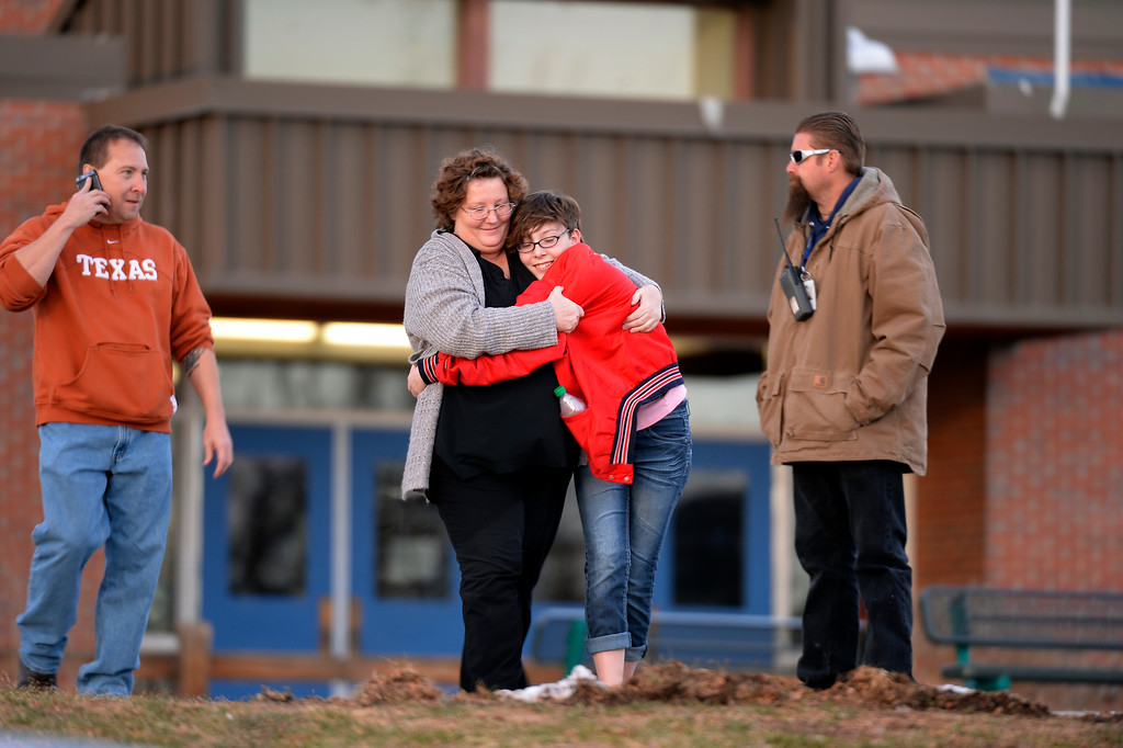 . CENTENNIAL, CO -  A student leaves Euclid Middle School with her parents after getting bused their from Arapahoe High School December 13, 2013. A gunman at the school was targeting a teacher at the school. The gunman shot two students in the process and then turned the gun on himself. (Photo by John Leyba/The Denver Post)