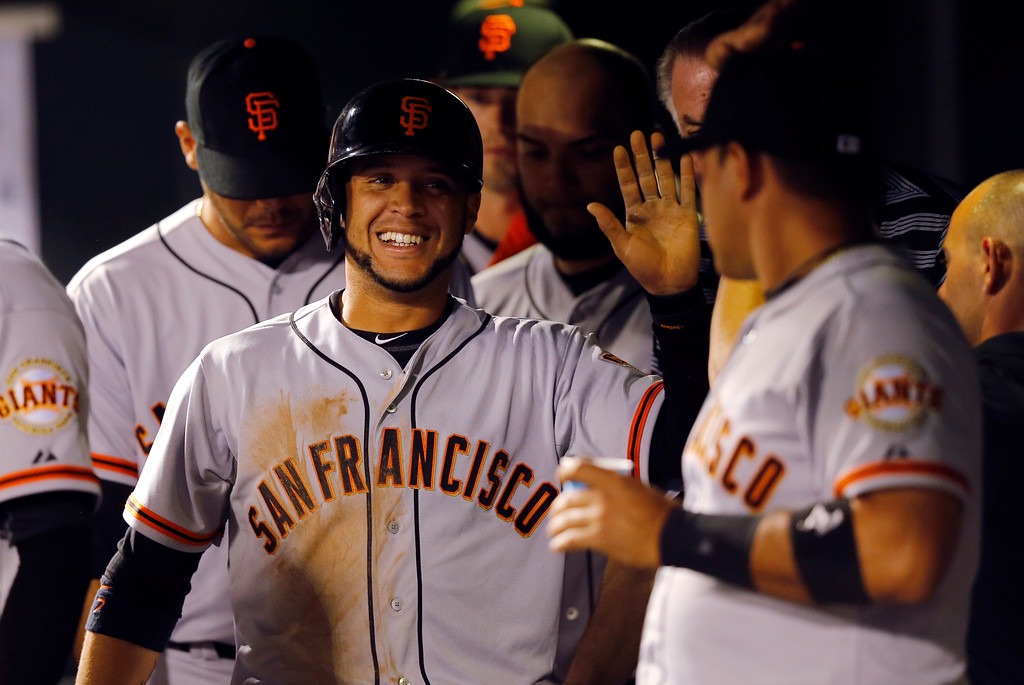 . San Francisco Giants\' Gregor Blanco smiles as teammates congratulate him after scoring on a Adam Duvall RBI single during the fifth inning of a baseball game against the Colorado Rockies Tuesday, Sept. 2, 2014, in Denver. (AP Photo/Jack Dempsey)