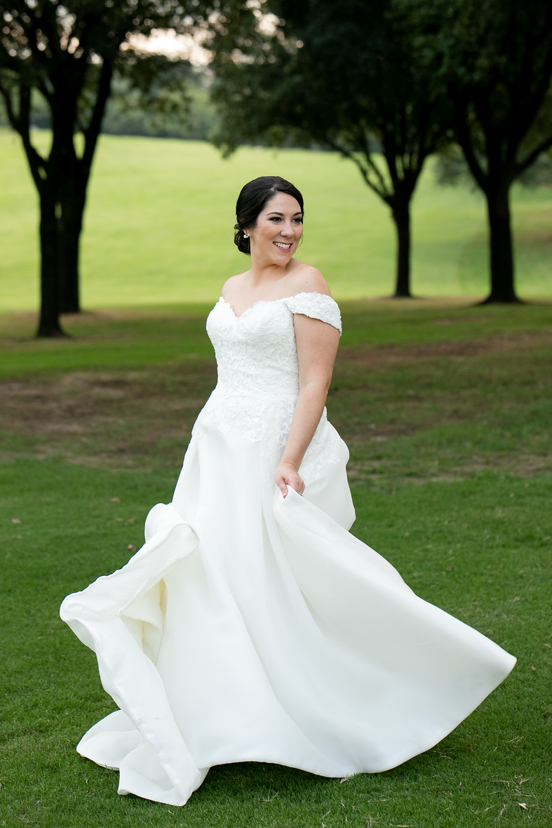 bride twirling her dress as she smiles towards her groom standing on a golf course