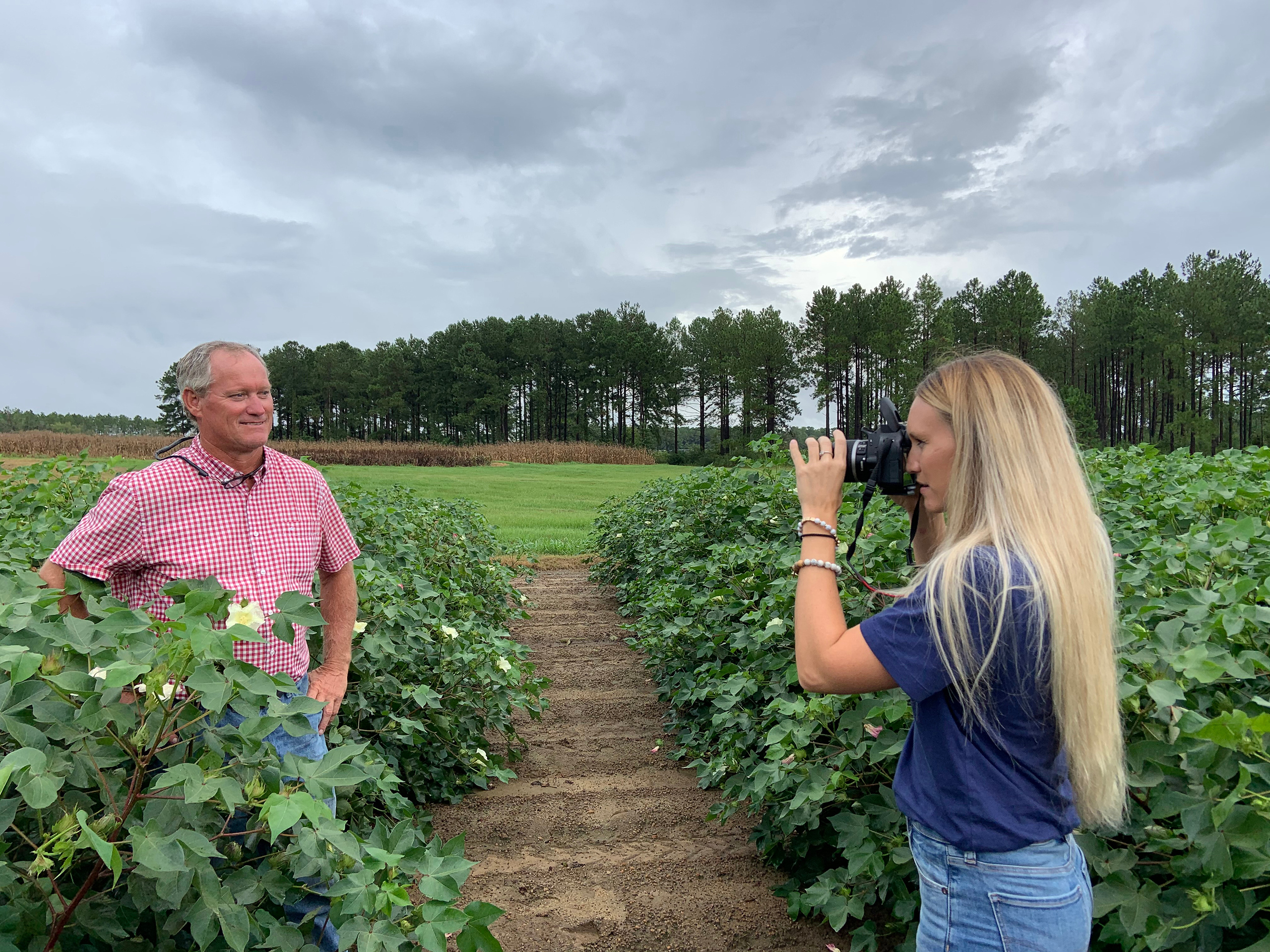 Caroline Snider takes a picture of Dr. Phillip Roberts, professor and extension entomologist for the University of Georgia in a cotton field.