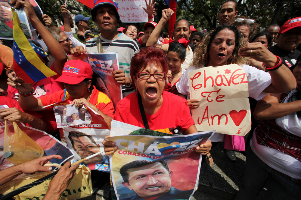 Description of . Supporters of Venezuela's President Hugo Chavez celebrate his return at Bolivar Square in Caracas, Venezuela, Monday, Feb. 18, 2013. Chavez returned to Venezuela early Monday after more than two months of treatment in Cuba following cancer surgery, his government said, triggering street celebrations by supporters who welcomed him home while he remained out of sight at the Carlos Arvelo Military Hospital in Caracas, where he will continue his treatment. (AP Photo/Fernando Llano)