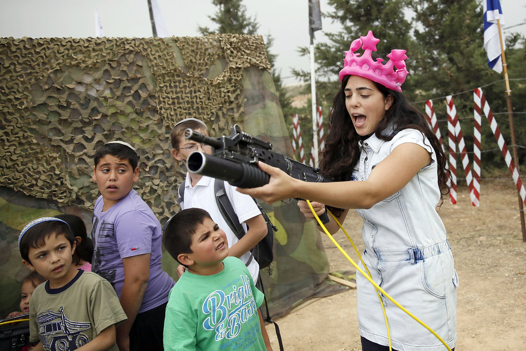 . An Israeli woman holds up an M-16 rifle during a traditional military weapon display to mark the 66th anniversary of Israel\'s Independence at the West Bank settlement of Efrat on May 6, 2014 near the biblical city of Bethlehem. Israelis are marking Independence Day, celebrating the 66th year since the founding of the Jewish State in 1948 according to the Jewish calendar. AFP PHOTO/GALI TIBBON