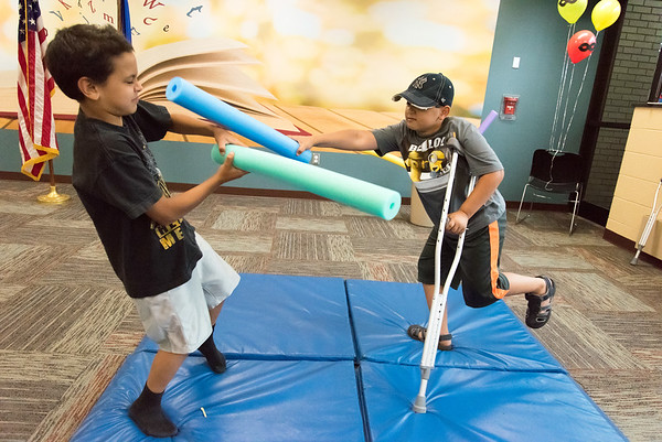 06/28/18 Wesley Bunnell | Staff Adam Tartt, L age 9, plays pool noodle jousting with Andy Rivera, age 9, at the Tween Time Olympics at the New Britain Public Library on Thursday afternoon. The event is designed to bridge the gap from youth to teen events in the library.