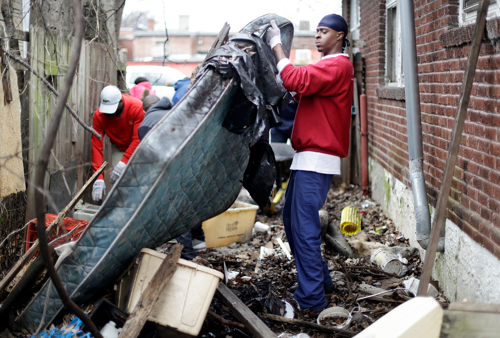 . Brandon Nelson helps to clear trash from a vacant house and yard on  Martin Luther King Jr. Day, Monday, Jan. 16, 2017, in Memphis, Tenn. Residents of the city where civil rights leader the Rev. Martin Luther King Jr. was killed are honoring his legacy with neighborhood clean-up events and a daylong celebration at the National Civil Rights Museum. (AP Photo/Mark Humphrey)