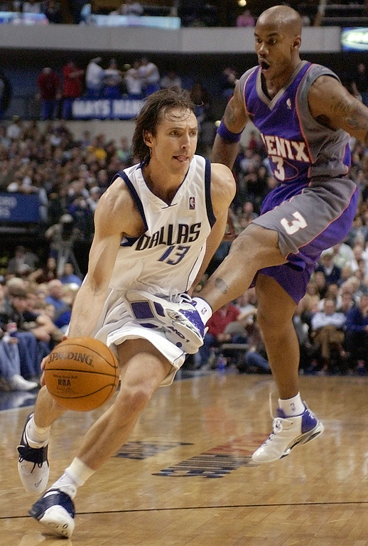 . Dallas Mavericks\' Steve Nash (13) drives through an accidental kick by Phoenix Suns\' Stephon Marbury (3) during the second half Saturday, March 22, 2003, in Dallas.  (AP Photo/Tony Gutierrez)