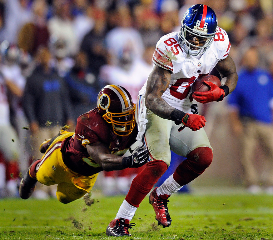 . Washington Redskins inside linebacker London Fletcher reaches to stop New York Giants tight end Martellus Bennett (85) during the first half of an NFL football game in Landover, Md., Monday, Dec. 3, 2012. (AP Photo/Nick Wass)