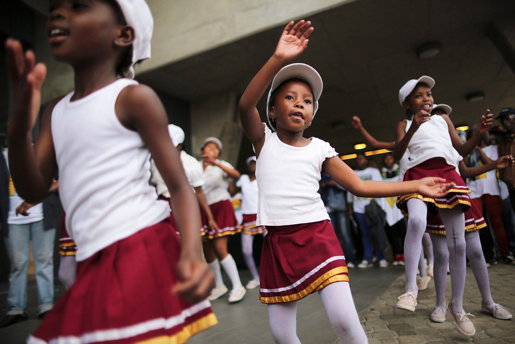 . Young South African girls dance during the memorial service for the late South African president Nelson Mandela at the First National Bank (FNB) Stadium in Soweto, Johannesburg, South Africa, 10 December 2013. Nobel Peace Prize winner Nelson Mandela died at the age of 95 on 05 December 2013.  EPA/DAI KUROKAWA