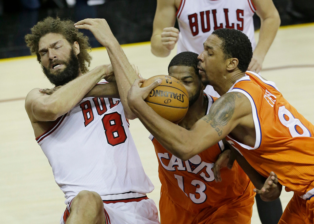 . Chicago Bulls\' Robin Lopez, left to right, Cleveland Cavaliers\' Tristan Thompson and Channing Frye battle for the ball in the second half of an NBA basketball game, Wednesday, Jan. 4, 2017, in Cleveland. (AP Photo/Tony Dejak)