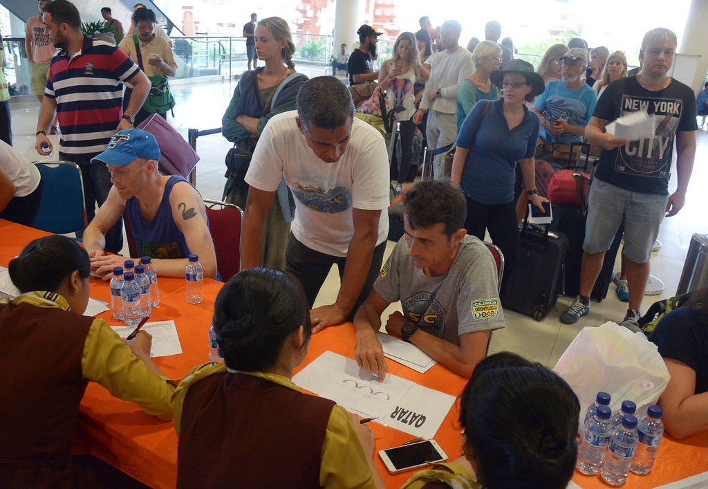 . Passengers talk to ground crew as their flights are cancelled at Ngurah Rai International Airport in Bali, Indonesia, Tuesday, Nov. 28, 2017. Indonesia\'s disaster mitigation agency says the airport on the tourist island of Bali is closed for a second day due to the threat from volcanic ash. (AP Photo/Ketut Nataan)