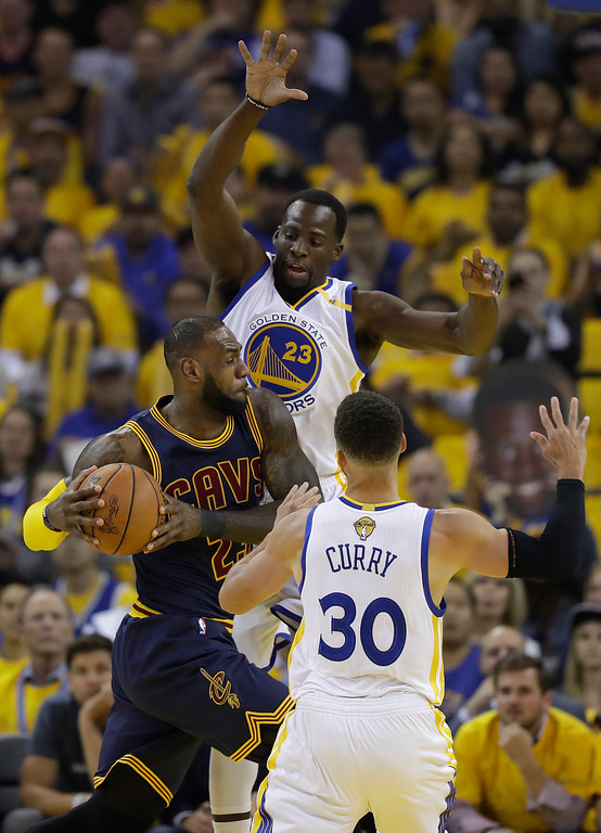 . Cleveland Cavaliers forward LeBron James, center, drives between Golden State Warriors forward Draymond Green, top, and guard Stephen Curry (30) during the first half of Game 1 of basketball\'s NBA Finals in Oakland, Calif., Thursday, June 1, 2017. (AP Photo/Marcio Jose Sanchez)