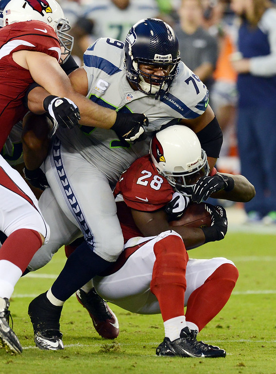 . GLENDALE, AZ - OCTOBER 17:  Red Bryant #79 of the Seattle Seahawks fights through a block and tackles Rashard Mendenhall #28 of the Arizona Cardinals at University of Phoenix Stadium on October 17, 2013 in Glendale, Arizona.  (Photo by Norm Hall/Getty Images)