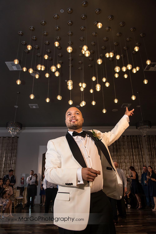 ggroom tossing garter during wedding reception at Sunol's Casa Bella