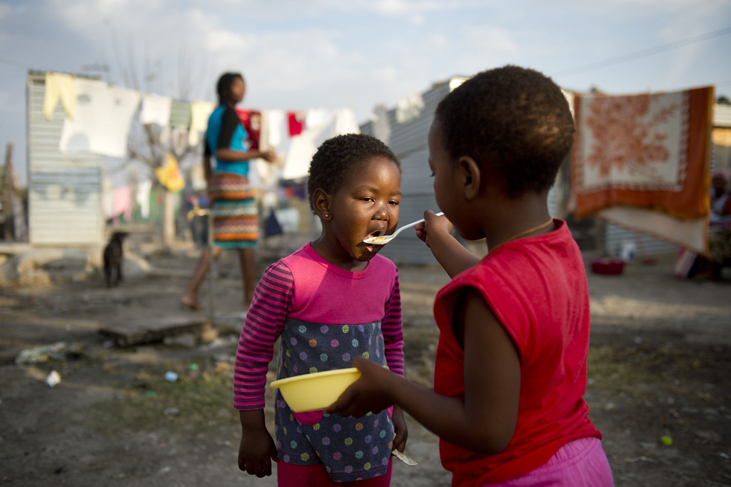 . A girl feeds her sister on July 9, 2013 in the Nkaneng shantytown next to the platinum mine, run by British company Lonmin, in Marikana. On August 16, 2012, police at the Marikana mine open fire on striking workers, killing 34 and injuring 78, during a strike was for better wages and living conditions. Miners still live in dire conditions despite a small wage increase.  ODD ANDERSEN/AFP/Getty Images