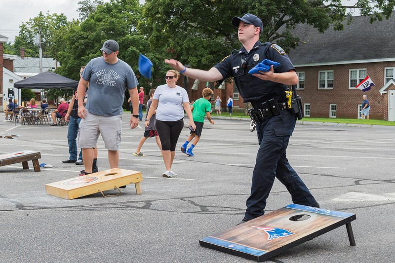 Police Officer Zach Frye plays a round of corn hole during Farmington's annual Hay Day Celebration in Farmington Saturday. [Scott Patterson/Fosters.com]