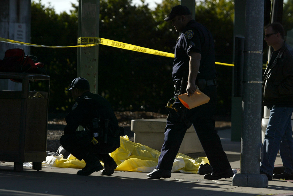 . A dead body lies covered on the sidewalk next to an AC Transit bus as police investigate the fatal shooting in the bus yard outside the Bay Fair BART station in San Leandro, Calif., on Saturday, Jan. 19, 2013. (Ray Chavez/Staff)
