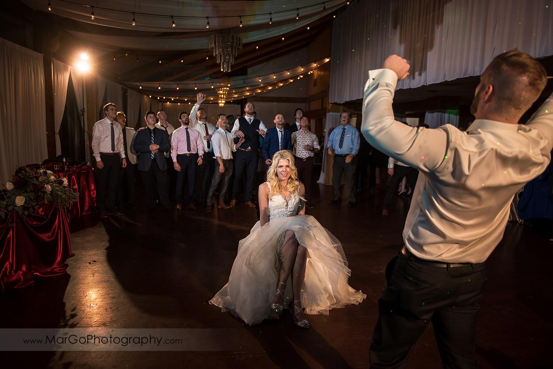 groom tossing garter during wedding reception at San Diego Marina Village