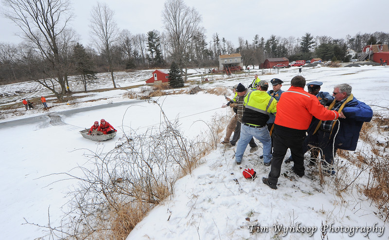 Firefighters and New Jersey State Police pull on a tow line attached to the boat and pull the other firefighters and doe to the edge of the pond.