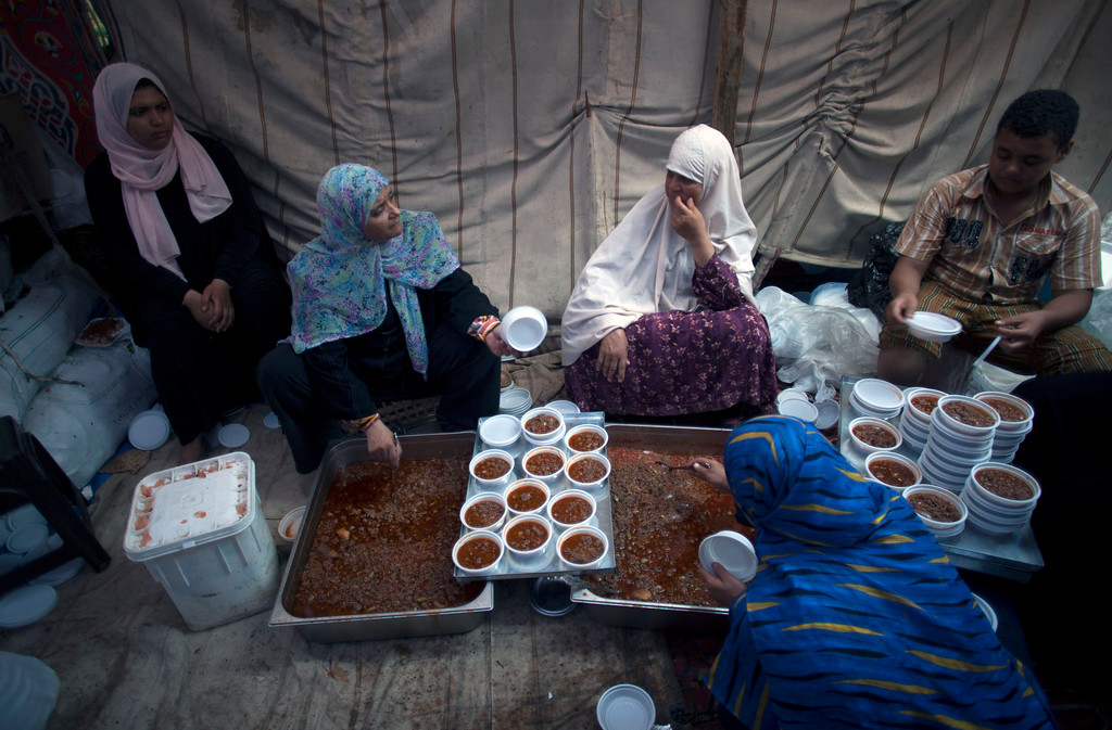 . Supporters of Egypt\'s ousted President Mohammed Morsi serve food on plastic dishes to distribute to protesters outside Rabaah al-Adawiya mosque, where they have installed a camp and held daily rallies at Nasr City, Cairo, Egypt, Tuesday, Aug. 13, 2013. Instead of rushing for the exits, Islamist supporters of Egypt\'s ousted president are replacing tents with wooden huts in their sprawling Cairo encampment. Barbershops have sprung up and many tents now have satellite dishes. (AP Photo/Khalil Hamra)