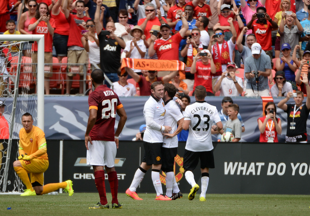 . Wayne Rooney (10), Juan Mata (8) and Tom Cleverley (23) of Manchester United celebrate Rooney\'s 2nd goal of the game against AS Roma in Guinness International Champions Cup 2014 at Sports Authority Field at Mile High in Denver, Colorado, July 26, 2014. (Photo by Hyoung Chang/The Denver Post)