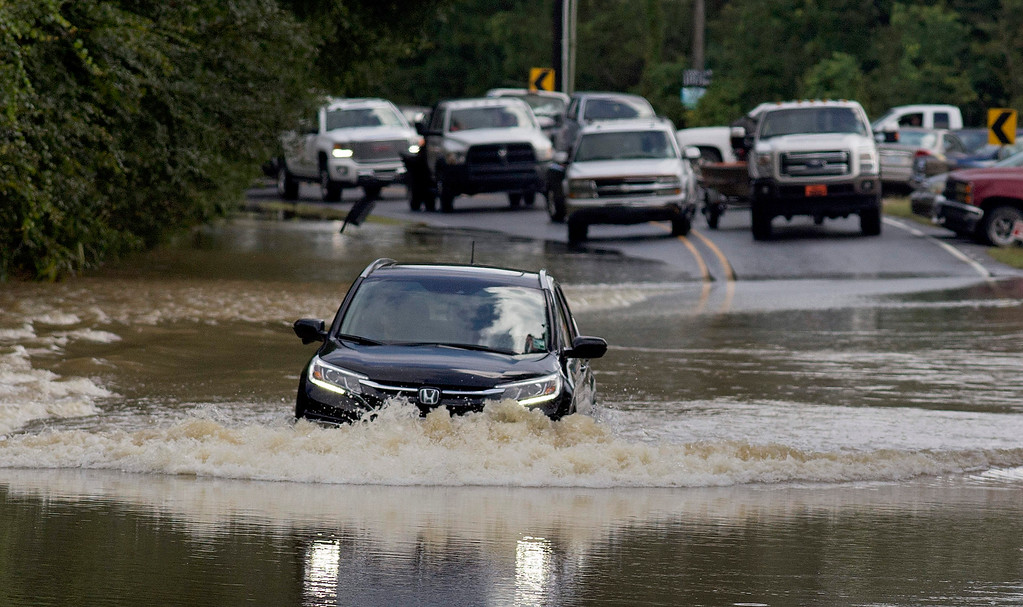 . Motorists try to navigate deep water flowing over a road in Walker, La., Monday, Aug. 15, 2016. Although some flood waters have receded roads continue to be difficult to pass with private vehicles. (AP Photo/Max Becherer)